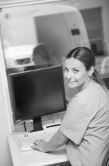Young female doctor smiling working at monitor of mri machine sc
