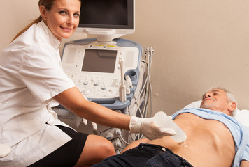 Happy woman doctor analyzing male patient with abdomen ultrasoun