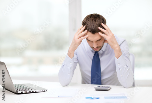 canvas print picture stressed businessman with laptop and documents