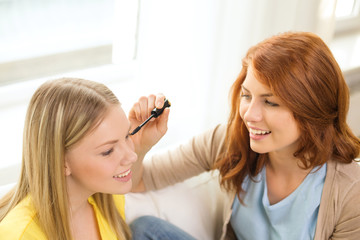 two smiling teenage girls applying make up at home