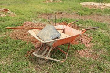 old wheelbarrow with sand and equipment