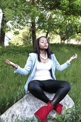 Stylish woman meditates in green nature