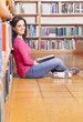 Portrait of a smiling young student reading a book in a library