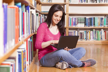 Happy smiling female student working with laptop in library