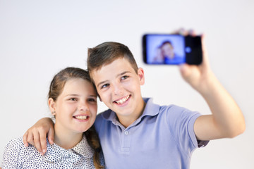 A boy and a girl taking a self portrait with smart phone against