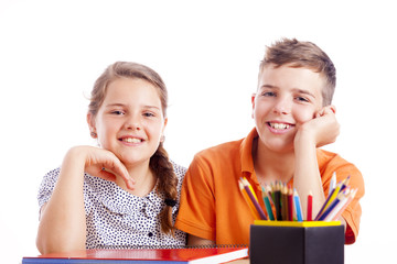 Portrait of two school kids at the desk, isolated on white backg