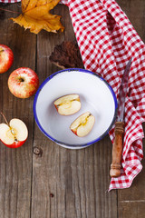 Autumn still life with apples over rustic wooden background