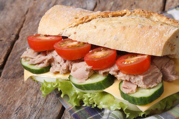 tuna sandwich with vegetables and cheese closeup on wooden