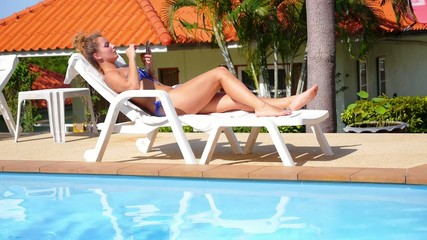 Young Beautiful Woman in Bikini Relaxing on a Deckchair Using