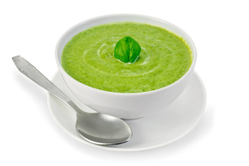 Soup puree with spinach in bowl and spoon