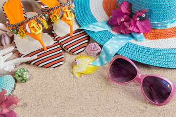 Sandals, blue hat and pink sunglasses on the sand. Summer beach