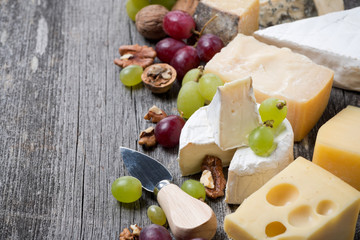 cheeses, grapes and walnuts on a wooden background, horizontal