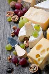 cheeses, grapes and walnuts on a wooden background, top view