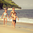 three little kids running on the beach
