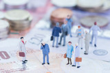 Miniature business people on Pound Sterling banknotes