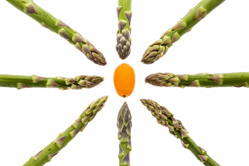 Eight asparagus tips aiming at one kumquat