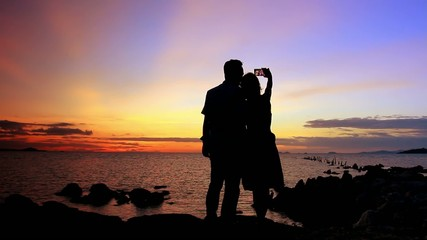 Silhouette couple in love taking self-portrait on the phone