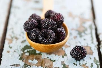 black raspberries in wooden spoon