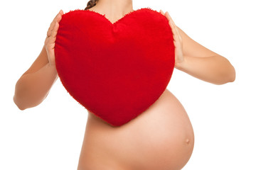 pregnant woman holding  heart symbol over white