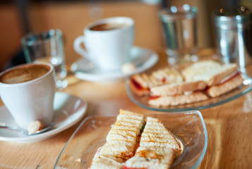 Delicious toasted mozzarella and tomato sandwich with hot coffee