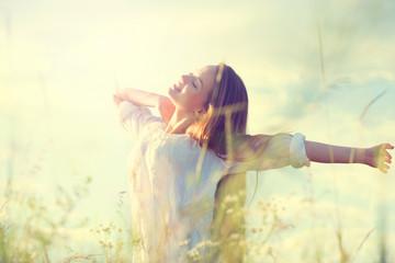 Teenage model girl in white dress having fun on summer field