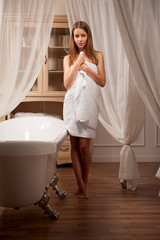 Cute young woman in bathroom interior
