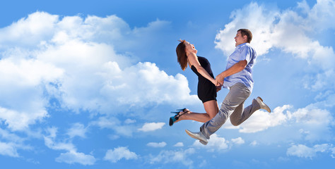 Cheerful loving couple in a jump against the blue sky background