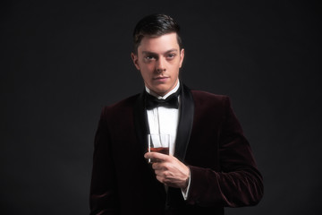 Well dressed good looking business man holding glass of whiskey.