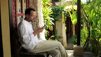 Young man with smartphone sitting on bench in front of country h