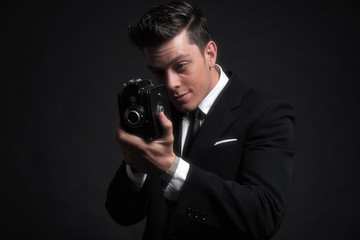 Retro fifties male photographer with vintage camera. Wearing bla