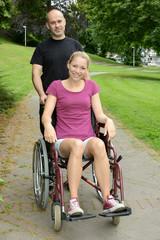 Frau im Rollstuhl bei Spaziergang im Park