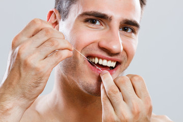 Young man using dental floss