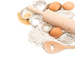 baking ingredients eggs, flour, sugar and cookie cutters over wh