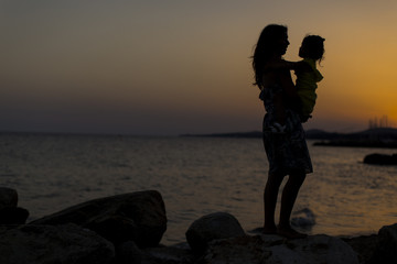 Mother and daughter at the beach at sunset