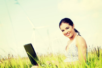 Teen with laptop computer next to wind turbine.