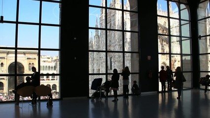 Tourists looking at the duomo through a window in Milan