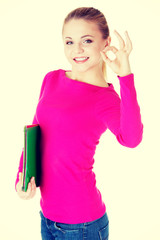 young casual woman student showin OK gesture.