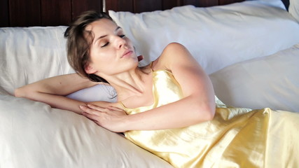 Woman waking up from sleep on big comfortable bed