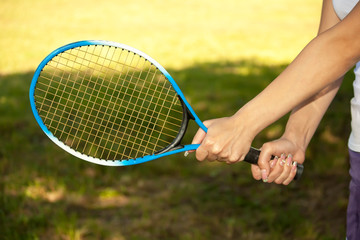 female hands holding a tennis racquet