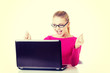 Young happy woman sitting in front of laptop.