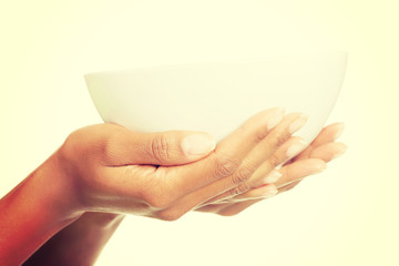 Female hands holding bowl.