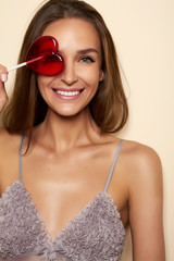 Lovely woman smiling covers one eye lollipop red heart