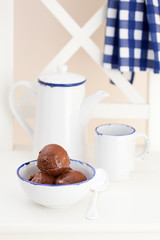 Chocolate ice cream in bowl on garden chair, selective focus