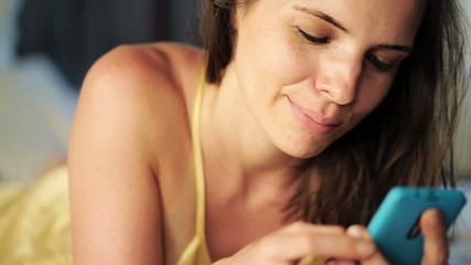 Elegant woman texting on smartphone while lying on bed