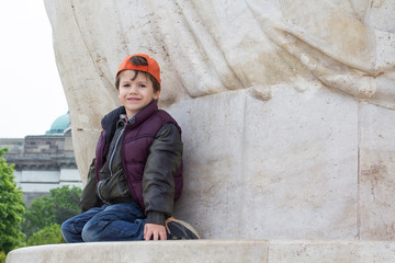Little boy sit at statue