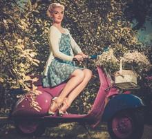 Belle femme blonde assise sur un rouleau rétro