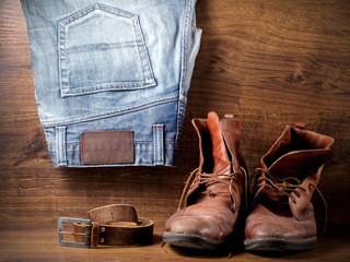 A pair of old boots, jeans and leather belt