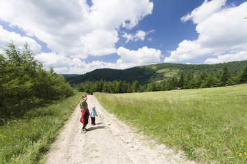 Woman with child hikes mountain patch, Gorce Mountains, Poland