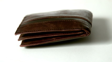 Brown leather wallet falling on white surface