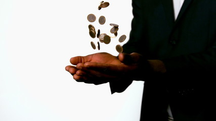 Businessman catching falling coins in hands